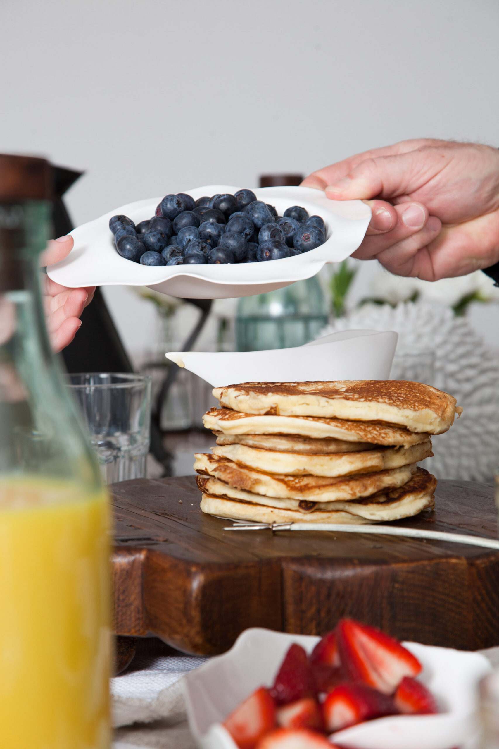 creative direction, lifestyle brand photography, food and prop styling. Creative photo of hands over table with pancakes.